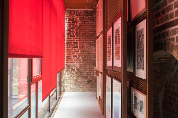 Interior of gallery space with red blinds retracted