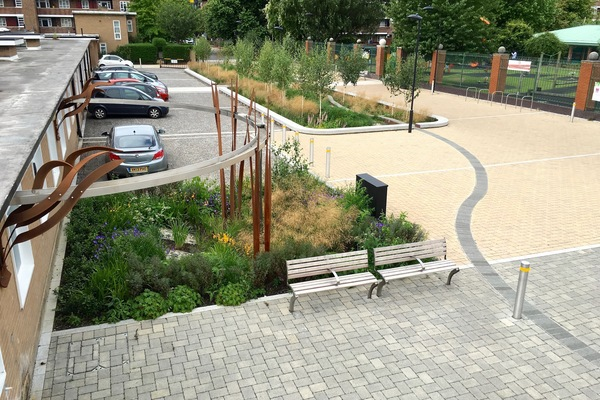 View from roof onto a raingarden, rain sculpture, permeable paving and the main rain basin