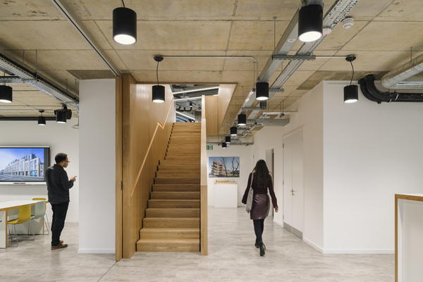 The feature timber staircase draws the eye upwards to the open plan office space