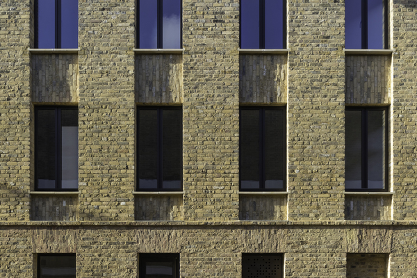 Facade of newly built 3 storey mixed use building, featuring reclaimed London stock bricks