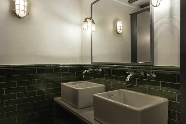 Belfast sink and glazed brick slips give bathrooms a unique aesthetic