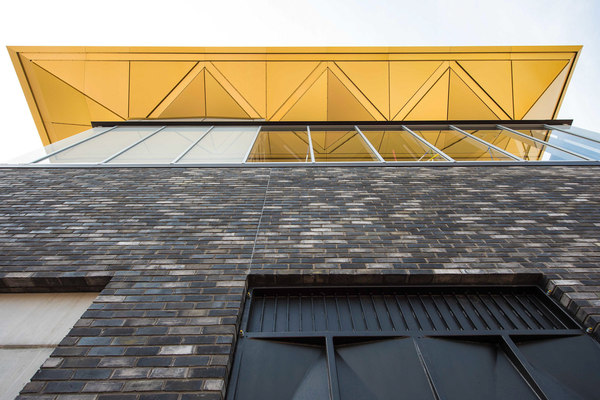 Golden anodized roof structure atop brick station building